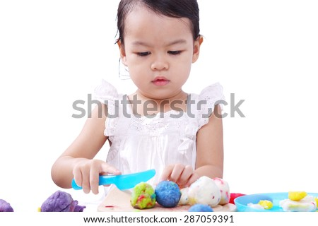 Asian Baby Girl Playing Colourful Dough. - stock photo