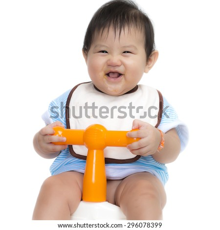 Asian baby girl sit on potty smiling happy on a white background. learning to use toilet. - stock photo