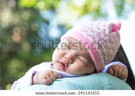 Asian baby girl sleeping on her mother shoulder - stock photo