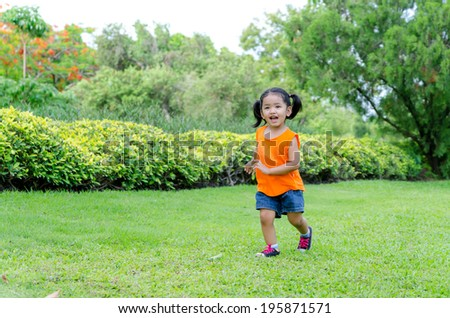 Asian baby girl smile and running in the garden - stock photo