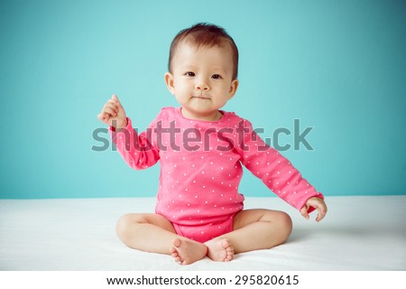 Asian baby girl wearing pink clothing - stock photo
