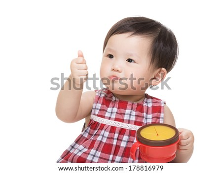 Asian baby girl with snack box and thumb up - stock photo