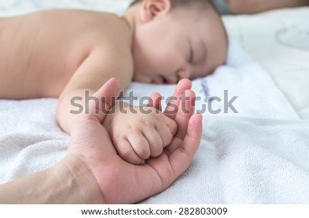 Asian baby hand on the adult hand