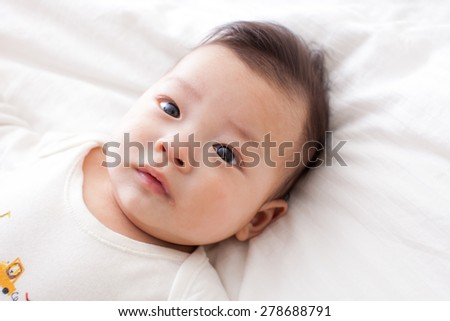 asian baby lay down on bed