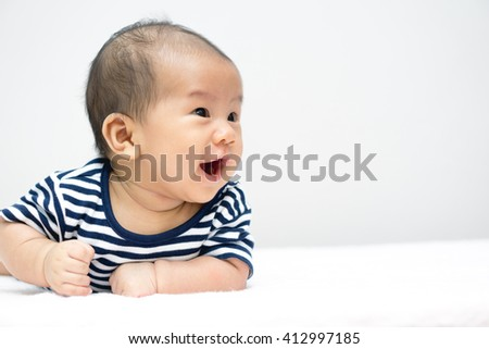 Asian baby lying on stomach and raising his head