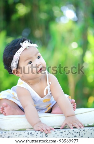 Asian baby sitting in the garden - stock photo
