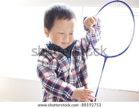 asian baby son playing badminton  at a sport center