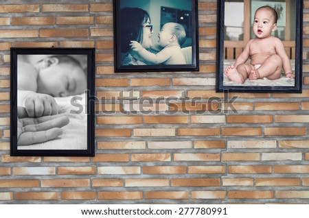 Asian baby with father and mother in the picture frame on brick wall background - stock photo