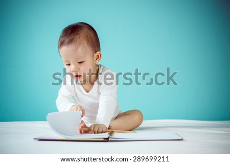 Asian baby writing in a book - stock photo