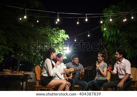Asian barbecue party men are singing their friends. at night - stock photo