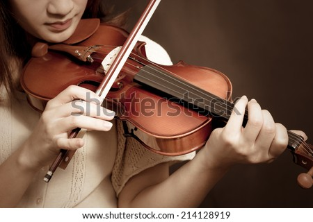 asian beautiful female musician playing violin on dark background
