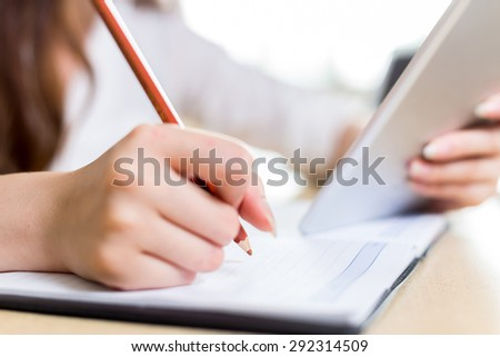Asian beautiful female student study in classroom with tablet - stock photo