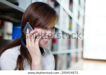 Asian beautiful female student using laptop and mobile phone in library - stock photo