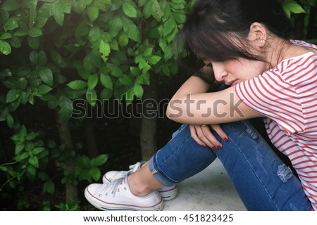 Asian beautiful sad young woman in the garden - stock photo