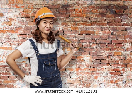 asian beautiful smiling female craftsman holding hammer on old brick wall background