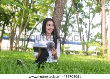 Asian  Beautiful smiling woman reading book in park