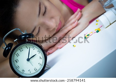 Asian beautiful woman in bed with tablets, medicine suffering insomnia, hangover, fever and headache at night - stock photo