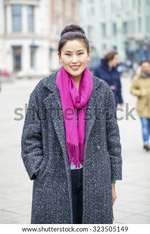Asian beautiful woman in stylish gray coat on a background of spring street - stock photo
