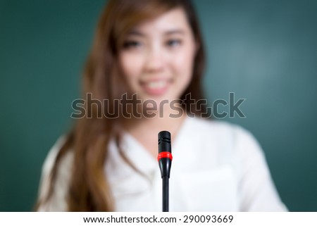 Asian beautiful woman speaking in front of blackboard with microphone.