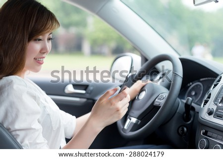 asian beautiful woman using mobile phone and driving car - stock photo