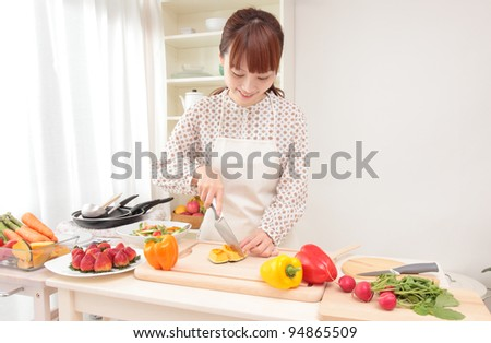Asian beautiful woman w is being prepared for cooking in the kitchen. - stock photo