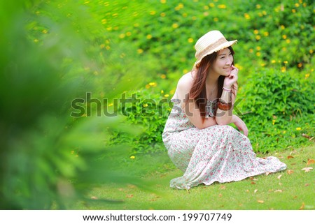 Asian beautiful young girl,wear floral maxi dress and hat, sitting on the ground at spring - stock photo