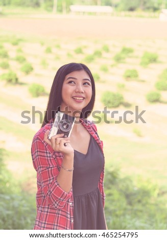 Asian beautiful young woman photographer taking photo in nature .Pretty girl is smile and happy in relax time,vintage tone