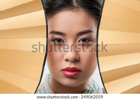 Asian beauty. Closeup portrait of attractive Asian woman wearing Japanese kimono and looking through two traditional hand fans  - stock photo