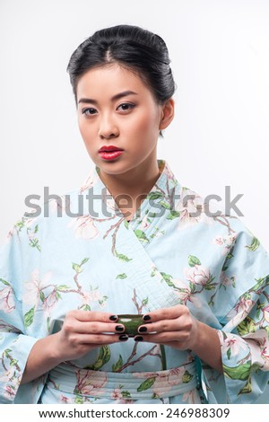 Asian beauty enjoying tea ceremony. Young beautiful Asian woman in traditional kimono holding cup of tea and looking at camera while standing against white background - stock photo