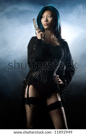 Asian beauty holding gun with smoke in background - stock photo