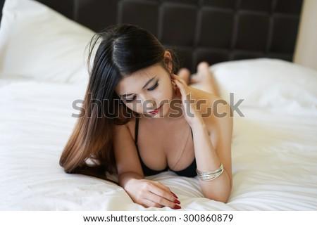 Asian beauty, portrait black bikini on white bed - stock photo