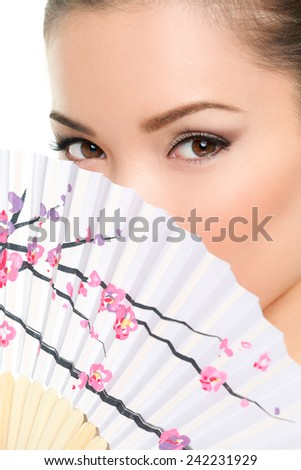 Asian beauty - seductive eyes woman chinese or japanese. Eye makeup Asian look with paper fan. Beauty portrait of mixed race Asian / Caucasian female model on white background. Close up on eyes. - stock photo