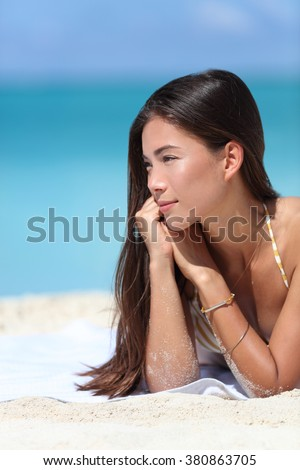Asian beauty woman relaxing on beach during summer vacation travel. Face closeup of Chinese Caucasian mixed race fashion model posing with bracelets and sun care makeup for skincare concept. - stock photo