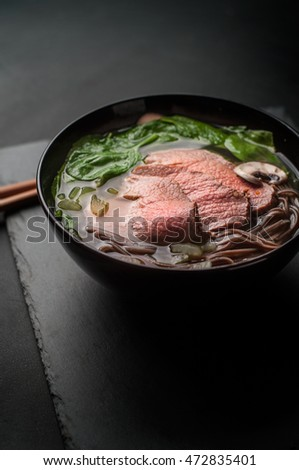 Asian beef noodle soup in black bowl