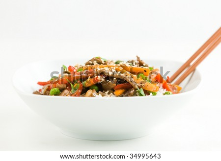 Asian beef stir-fry on rice with peppers carrots onions and peas in black bean sauce - stock photo