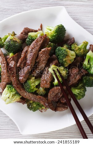 Asian beef with broccoli on a plate close-up and chopsticks. vertical top view
