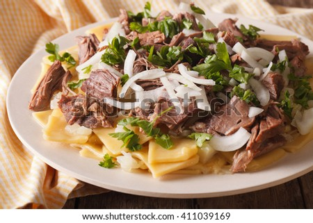 Asian beshbarmak - noodles with mutton and onion close-up on a plate on the table. horizontal - stock photo