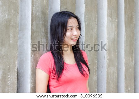 Asian black hair girl wearing pink shirt at the modern wall background