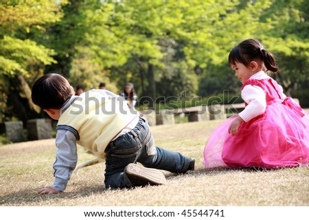 asian boy and girl playing at garden - stock photo