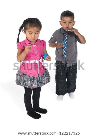 Asian boy and girl playing with bubble wand
