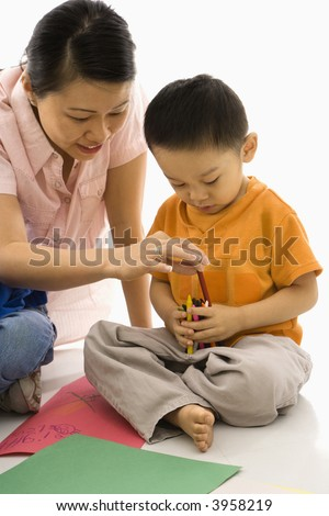Asian boy and mother coloring with crayons. - stock photo