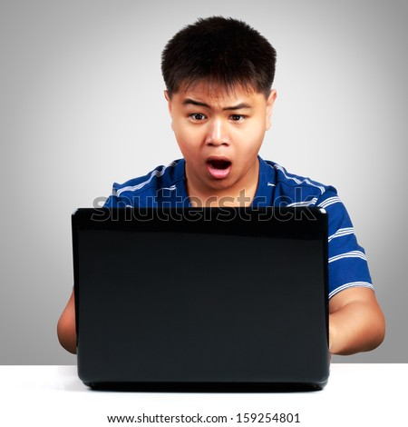 Asian boy at the computer surprised - stock photo