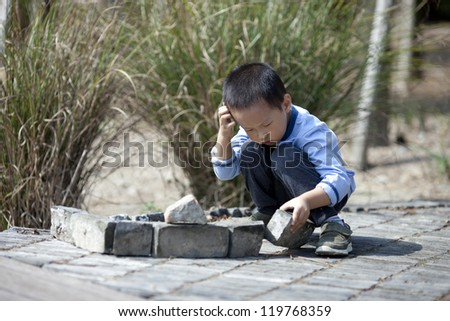 Asian boy building house by brick in a game