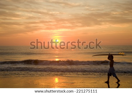 Asian boy carrying surfboard at beach