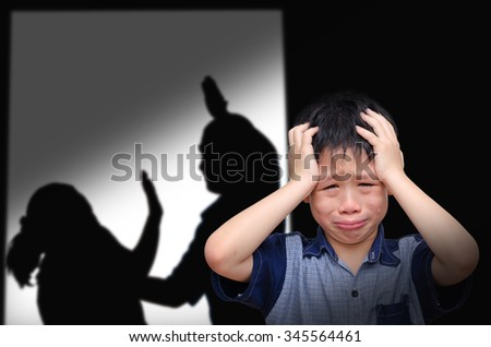 Asian boy crying with his parent fighting in background - stock photo