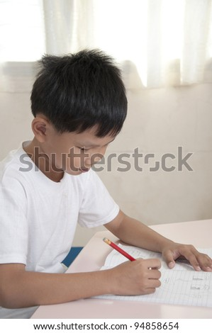 Asian boy do home work in classroom - stock photo