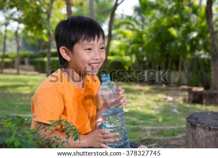 asian boy drink water thirsty tired park nature outdoors happy