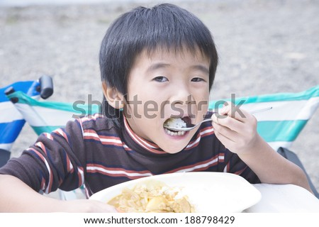 Asian boy eating curry and rice outdoors