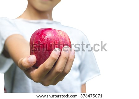 Asian boy hand holding red apple  on green natural background.