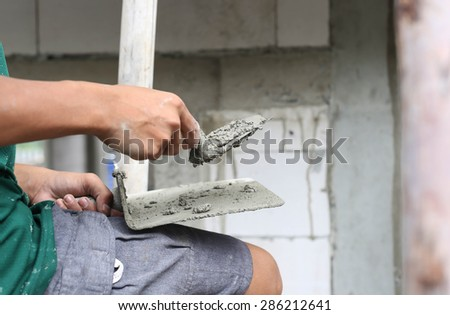 Asian boy hand using trowel with wet concrete plaster in building site - stock photo